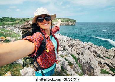 Happy woman backpacker traveler take a selfie photo on amazing ocean coast.Asturias, Spain.