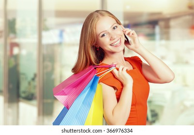 happy woman with  bags on a shopping, talking on the phone