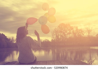 Happy woman with balloons in sunset
