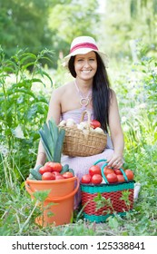 Happy woman with basket of harvested vegetables in garden