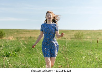 Happy woman with beautiful blonde hair smiling and running on the green meadow