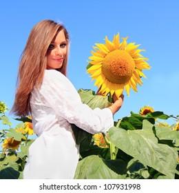 Happy woman in beauty field with sunflowers