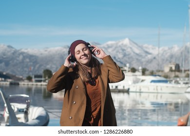 Happy Woman in a beige coat listens to music or a podcast and stands by the sea. Snow-capped mountains on the background in Montenegro