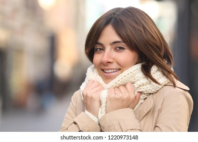 Happy woman being cold grabbing scarg and looking at camera in winter in the street