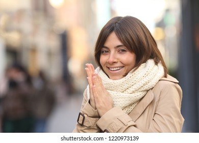 Happy woman being cold heating hands and looking at camera in the street in winter