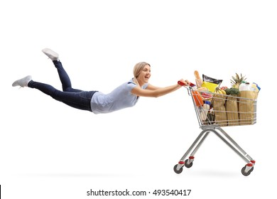 Happy woman being pulled by a shopping cart full of groceries isolated on white background