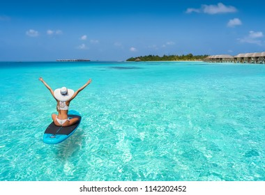 Happy woman in bikini enjoys the turquoise waters of the Maldives on a surfboard