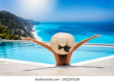 A happy woman in bikini and with hat sits in the swimming pool and enjoys the beautiful view to the turquoise sea of Lefkada island, Ionian Sea, Greece, during summer time