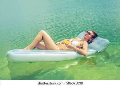 Happy woman in bikini lying on air bed in sea or ocean with a glass of orange alcohol cocktail. relaxing girl with healthy beverage on blue water texture. resort in summer time season.