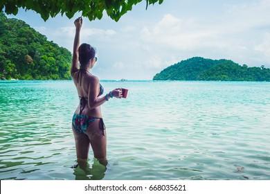 Happy woman in bikini relaxing on sea beach her hand holding cup of coffee, Andaman sea, Mu Koh Surin national park, Phangnga, Thailand