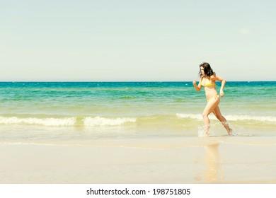 happy woman in bikini running on the beach