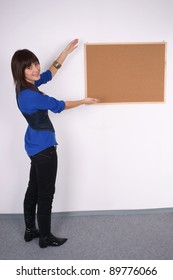 Happy woman with blank pin board. Full body shot.