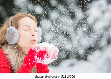 Happy woman blowing snow outdoors. Girl having fun in winter park