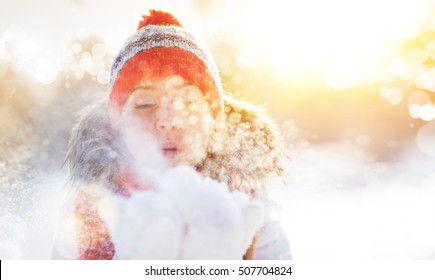 happy woman is happy and blowing snow in the winter nature