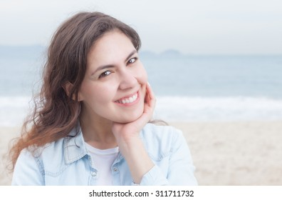 Happy woman in a blue blouse at phone at beach