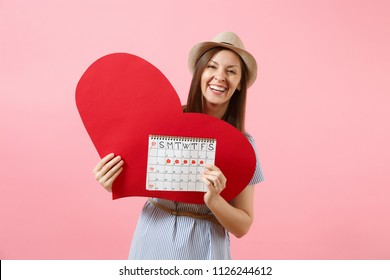 Happy woman in blue dress summer hat holding empty blank red heart, female periods calendar, checking menstruation days isolated on background. Medical healthcare gynecological concept. Copy space