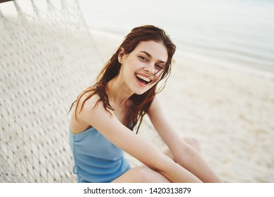 Happy woman in a blue swimsuit is lying on a lounger laughing