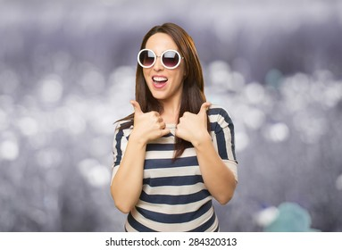 Happy woman with both thumbs up. She is wearing white sunglasses. Over abstract background