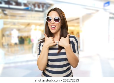 Happy woman with both thumbs up. She is wearing white sunglasses. Over shopping center background
