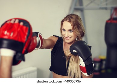 Happy woman boxer preparing in gym with instructor