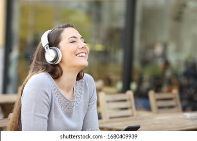 Happy woman breathing fresh air listening to music with headphones on a cafe terrace