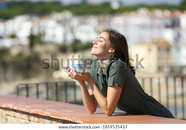 Happy woman breathing fresh air enjoying sun and drinking coffee from balcony in a beach town