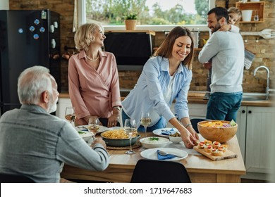 Happy woman brining food at the table while having family lunch in dining room.