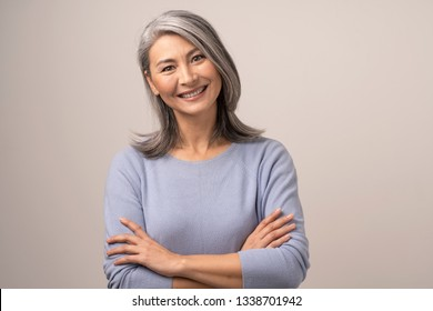 Happy Woman With Broad Smile And Crossed Arms. Cute Asian Grey-Haired Woman Broadly Smiles And Crosses Her Arms Posing At Studio On White Background. Portrait
