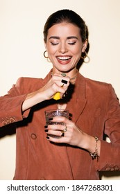 happy woman in brown blazer squeezing lemon in glass with alcohol cocktail on white