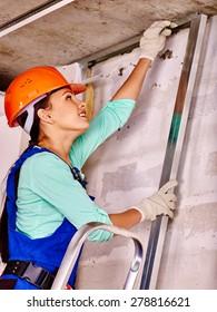 Happy woman in builder uniform and orange helmet at work.