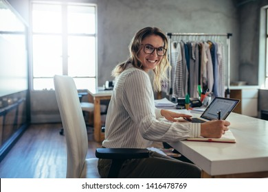 Happy woman business owner writing notes in diary. Online store working at her desk.