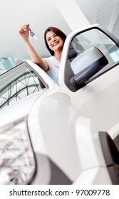 Happy woman buying a car and holding the keys