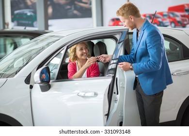 Happy woman buying a new car and salesman handling keys