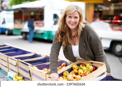 A happy woman buys a crate of apples at the weekly market