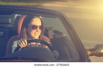 Happy woman in cabriolet car