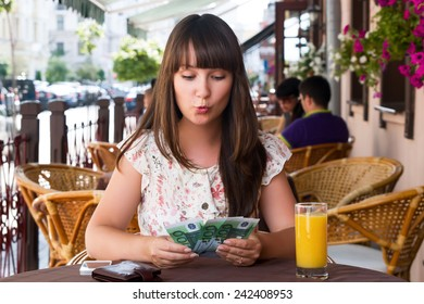 Happy woman in a cafe counting money