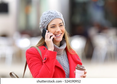 Happy woman calling on the mobile phone and holding a take away coffee in the street in winter