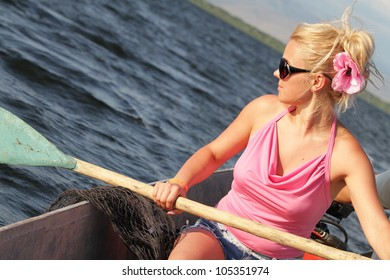 A happy woman in a canoe on a lake at sunset