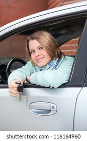 Happy woman in car window with ignition key