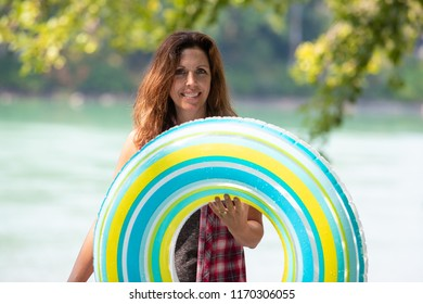 Happy woman carrying inflatable innertube