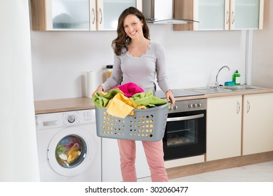 Happy Woman Carrying Laundry Basket In Kitchen Room