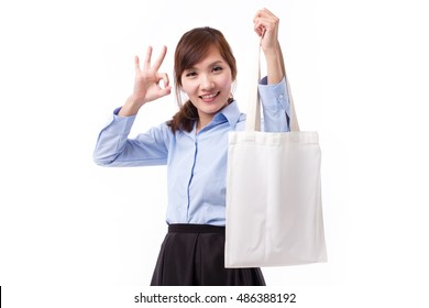 happy woman carrying reusable cotton bag giving ok hand sign gesture