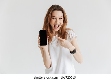 Happy woman in casual clothes showing blank smartphone screen and looking at the camera over grey background