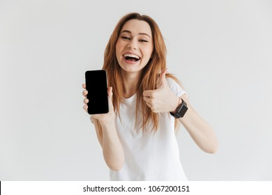 Happy woman in casual clothes with wristwatch showing blank smartphone screen and thumb up while looking at the camera over grey background