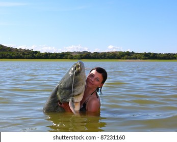 Happy woman with a catfish she has just caught