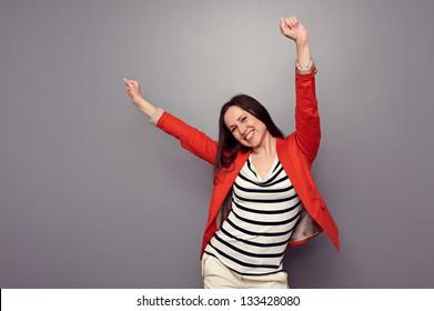 happy woman celebrating and dancing of joy winning. studio shot over dark background