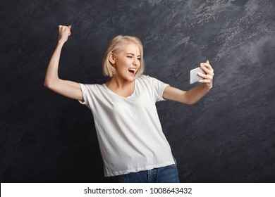 Happy woman celebrating success and reading good news on smartphone. Girl seeng exciting message on mobile at gray studio background, victory concept, copy space