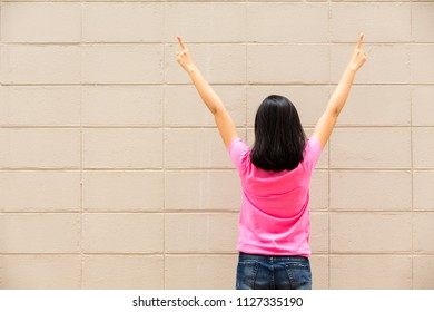Happy woman celebrating victory and raises his hands up on brick wall background
