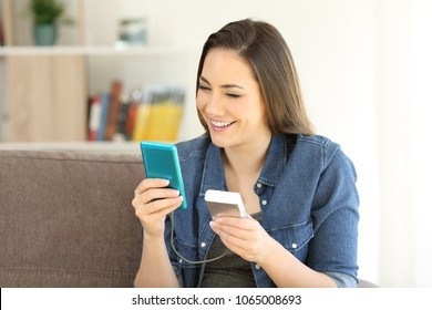 Happy woman charging a smart phone with a portable charger sitting on a couch at home