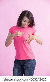 Happy woman check her chest with pink ribbon, great for prevention breast cancer concept